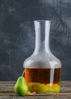 Bebida da cidra de pera com pera em uma garrafa na parede de madeira e suja, vista lateral.