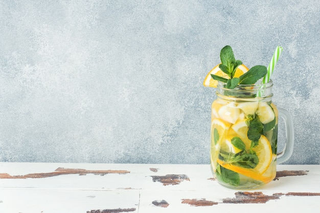 Bebida da limonada das folhas da água de soda, do limão e de hortelã no frasco no fundo claro.