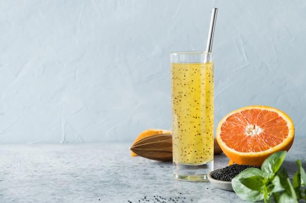 Bebida da semente da manjericão com suco de laranja no vidro no azul. fechar-se.