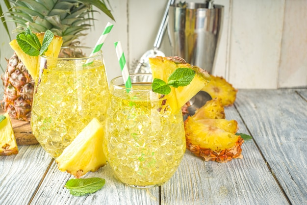 Bebida de abacaxi e limão, coquetel de limonada com abacaxi picado e rodelas, sobre fundo branco de madeira com folhas tropicais e lápis de bar