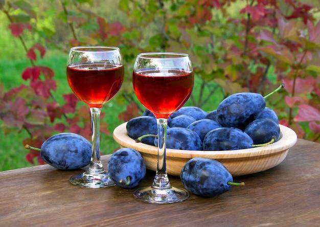 Bebida de ameixa em copo de vinho com ameixas em fundo natural