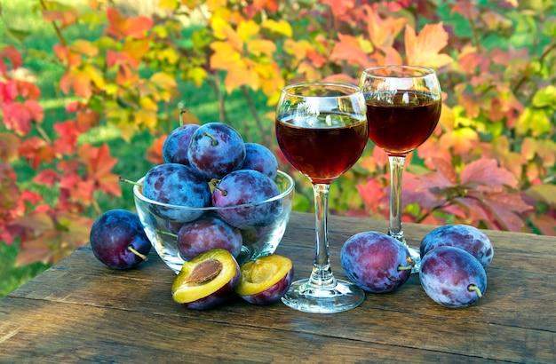 Bebida de ameixa em um copo de vinho com ameixas em um fundo natural em um dia ensolarado