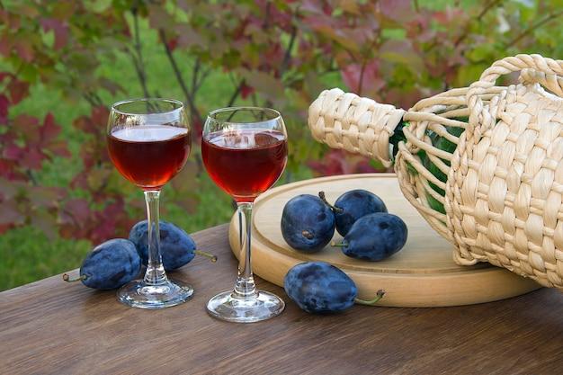 Bebida de ameixa em um copo de vinho em fundo natural