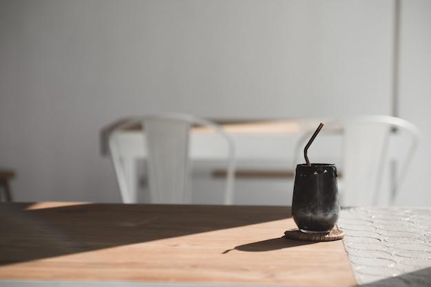 Bebida de bebida preta feita de carvão e leite na mesa de madeira de estilo vintage