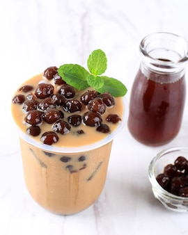 Bebida de bolha de açúcar mascavo. um copo de plástico de leite fresco e coberturas de boba / bolha de açúcar mascavo e coberto com biscoitos de chocolate na mesa de madeira.