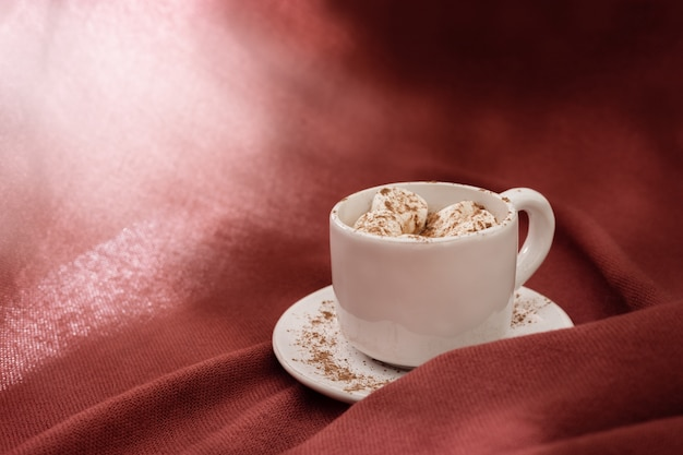 Bebida de cacau doce quente com marshmallow, luz do sol brilhante, texturizado fundo de têxteis
