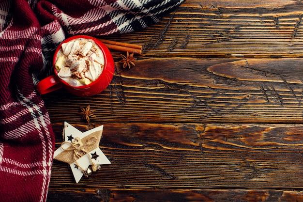 Bebida de café de inverno, cacau com chantilly e marshmallows em uma xícara de cerâmica vermelha