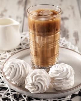 Bebida de café gelado com zéfiro caseiro doce café da manhã natureza morta, vertical