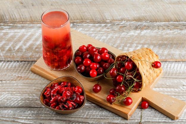 Bebida de cereja com cerejas, geléia em uma jarra na tábua de madeira e