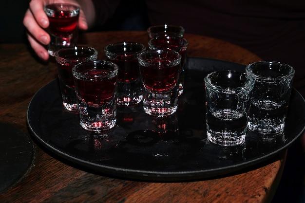 Bebida de cereja vermelha em copos de shot com as mãos - festa no bar