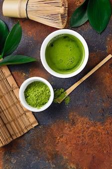 Bebida de chá matcha verde e acessórios de chá no escuro enferrujado