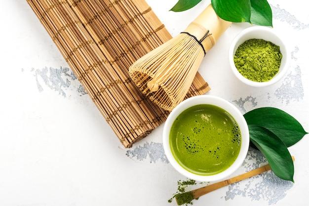Bebida de chá matcha verde e acessórios de chá no fundo branco