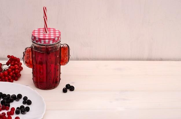 Bebida de chá vermelho em uma jarra com um canudo de bagas em um fundo branco de madeira