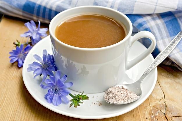 Bebida de chicória em um copo branco com uma flor e uma colher no pires, guardanapo sobre um fundo de tábuas de madeira