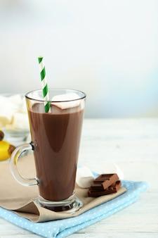 Bebida de chocolate com marshmallows na caneca, com fundo de madeira