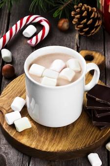 Bebida de chocolate quente de natal com creme e marshmallows numa superfície de madeira
