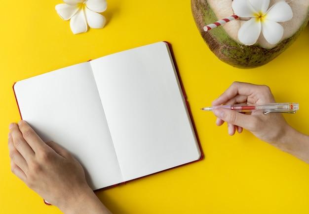 Bebida de coco fresco, abra o bloco de notas vazio e as mãos da mulher em fundo amarelo