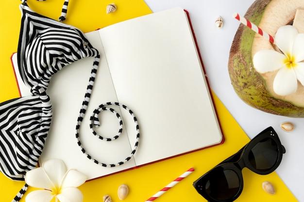 Bebida de coco fresco, abra o bloco de notas vazio, maiô e óculos de sol em fundo amarelo.