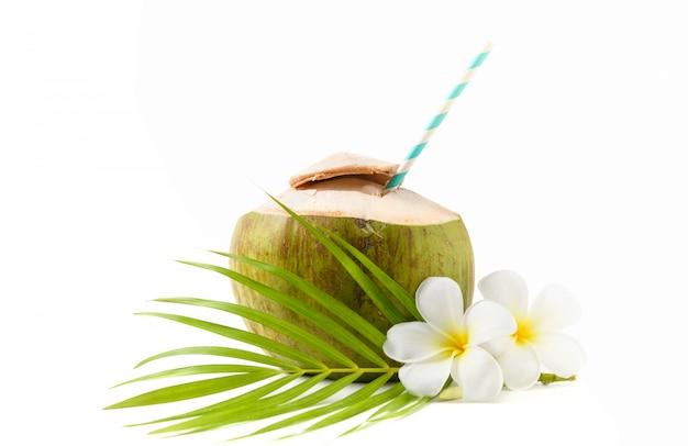 Bebida de coco fresco com flor de plumeria e palha de papel isolado