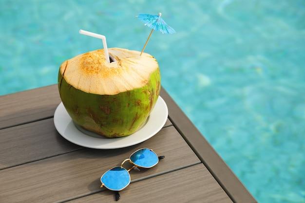 Bebida de coco fresco e óculos de sol na mesa ao lado da piscina