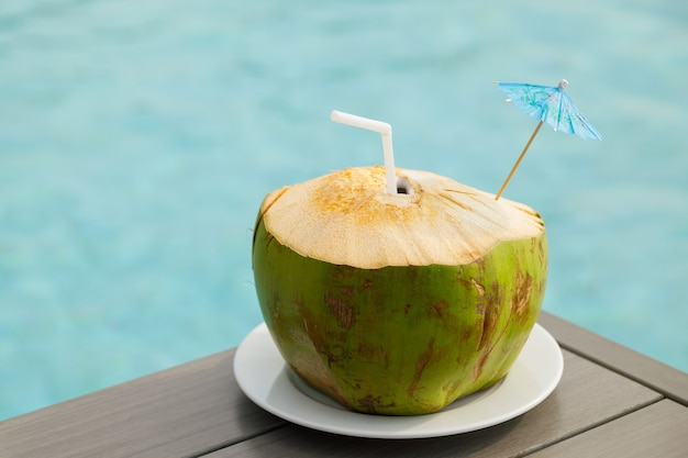 Bebida de coco fresco na mesa ao lado da piscina