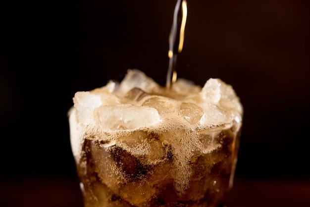 Bebida de cola fresca fria gaseificada com gás sendo derramada no copo
