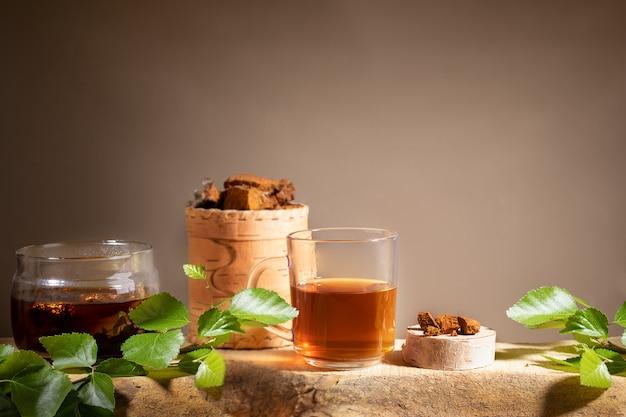 Bebida de cura de bétula chaga cogumelo, pedaços de cogumelo chaga, galhos na prancha de madeira em pano de fundo bege. copie o espaço.