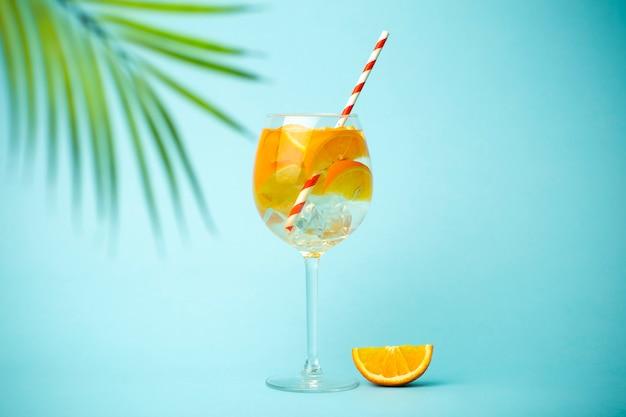Bebida de desintoxicação de verão em um fundo azul. bebida gelada de verão com laranjas e gelo em um fundo colorido vazio