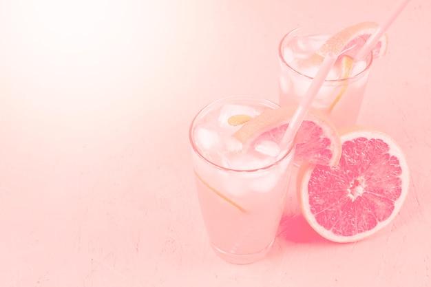 Bebida de dieta saudável de verão fresco e toranja no fundo rosa