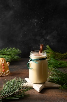 Bebida de gemada nas férias de natal em frasco de vidro com pão de gengibre em fundo marrom