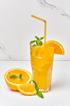 Bebida de laranja com hortelã e gelo em um copo close-up na superfície da luz