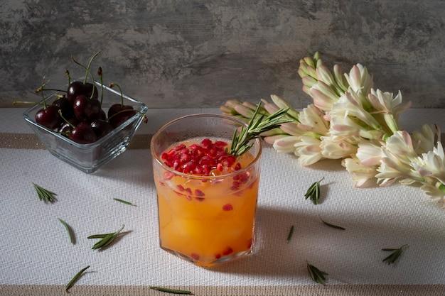 Bebida de laranja com romã vermelha e um ramo de alecrim em uma mesa acompanhada de cerejas