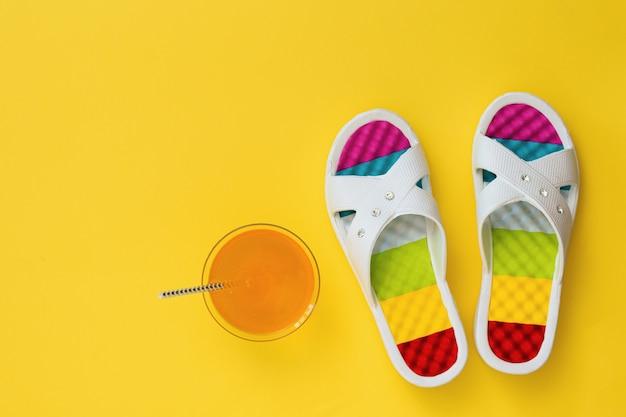 Bebida de laranja e ardósias com solas coloridas em fundo amarelo. o conceito de férias de verão. postura plana. a vista do topo.
