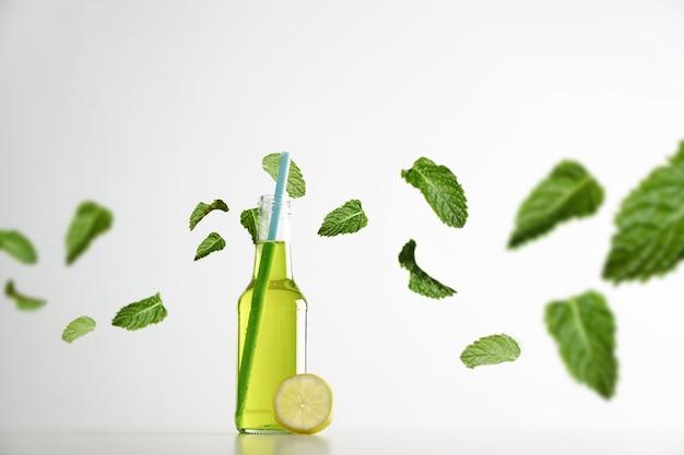 Bebida de limão fresco à base de ervas dentro de uma garrafa de coquetel transparente aberta com canudo azul dentro