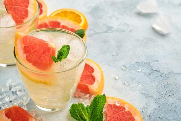 Bebida de limonada feita de toranja, água com gás e folhas de hortelã com gelo na superfície de concreto azul claro. vista do topo.