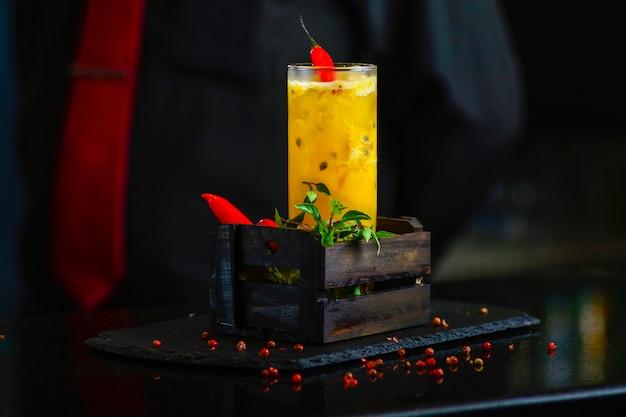 Bebida de maracujá com pimenta vermelha em um escuro. caipirinha de maracujá brasileira