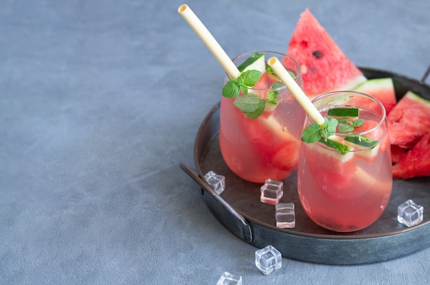 Bebida de melancia de verão em dois copos com canudos ecológicos e frutas fatiadas em uma bandeja de metal