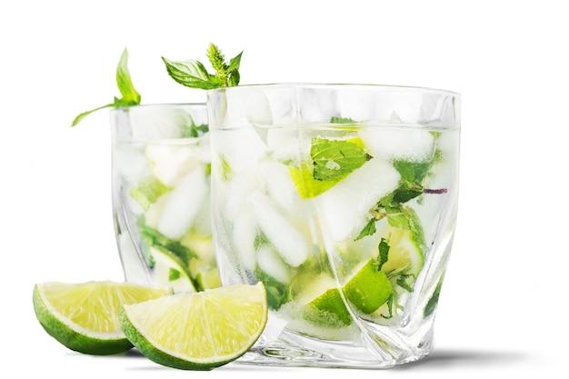 Bebida de mojito gelado, copo de álcool isolado sobre fundo branco, hortelã fresca e fatias de limão,
