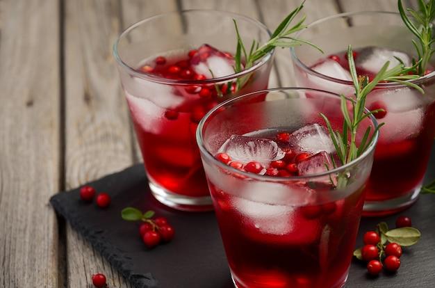 Bebida de refrescamento fria com arandos e alecrins em um fundo de madeira.