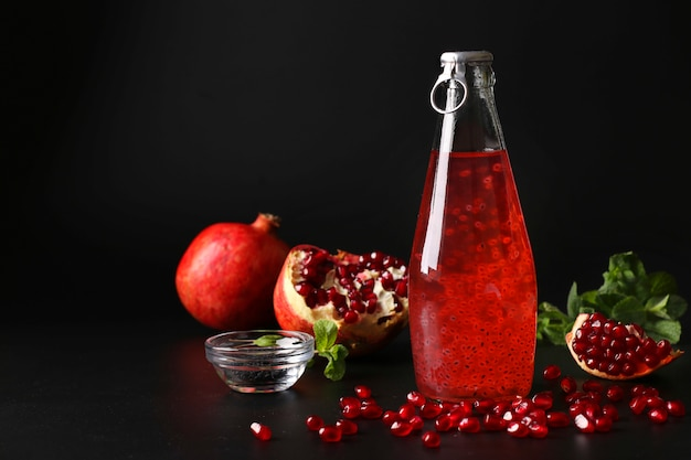 Bebida de romã na moda com sementes de manjericão em garrafa em fundo preto, closeup