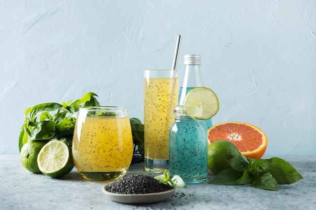 Bebida de sementes de manjericão com suco de laranja e tropical em vidro na luz de fundo. fechar-se.