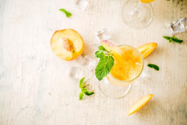 Bebida de verão com álcool frio, coquetel bellini de pêssego gelado com folhas de hortelã, superfície de concreto leve