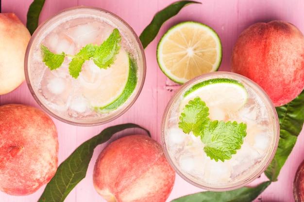 Bebida de verão com álcool frio, coquetel bellini de pêssego gelado com folhas de hortelã