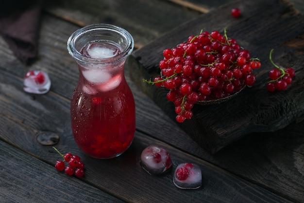 Bebida de verão com espumante branco. coquetel de frutas caseiro refrescante ou ponche com champanhe, groselha, cubos de gelo e folhas de hortelã em uma madeira escura