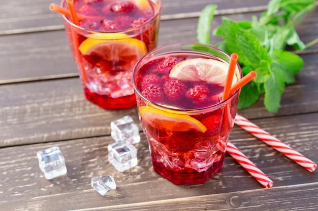 Bebida de verão com framboesas, limão e gelo em uma mesa de madeira velha