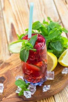 Bebida de verão com framboesas, limão e gelo em uma velha mesa de madeira