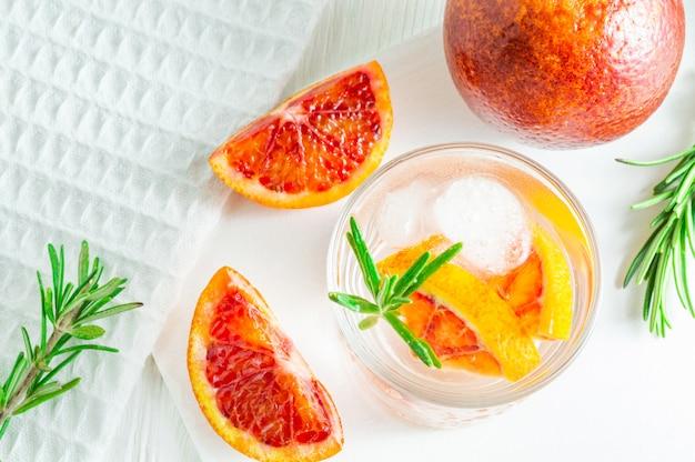 Bebida de verão com laranja de sangue e alecrim no fundo branco de madeira