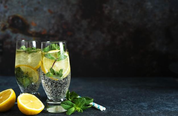 Bebida de verão com limão e hortelã em uma mesa escura.