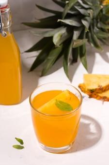 Bebida de verão de abacaxi kombuchá fermentado em um prato branco ao lado dos ingredientes. foto vertical