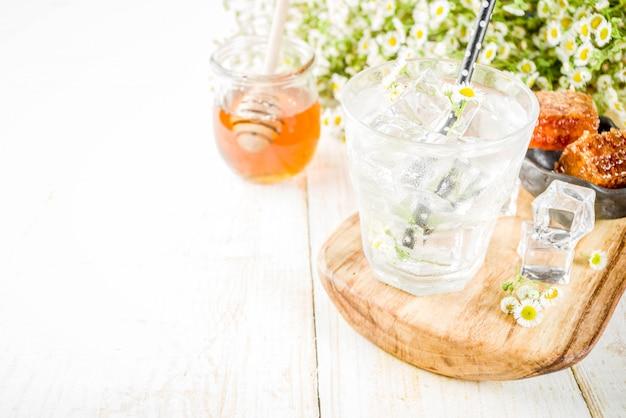 Bebida de verão dieta orgânica desintoxicação, infusão de água com camomila e mel, na mesa de madeira branca, com flores de camomila e mel em uma jarra. copie o espaço